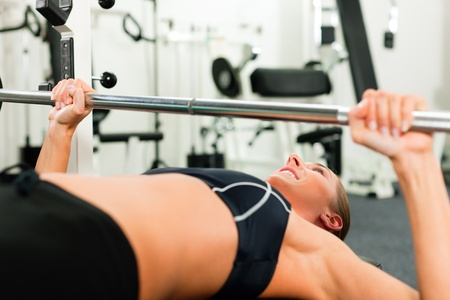 Woman in gym exercising for better fitness with a barbell   photo