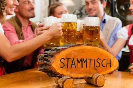 tracht: Inn or pub in Bavaria - group of five young men and women in traditional Tracht drinking beer and having a party with beer