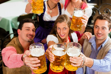 Inn or pub in Bavaria - group of five young men and women in traditional Tracht drinking beer and having a party with beer photo