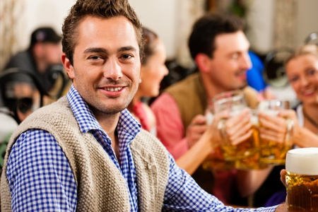 Inn or pub in Bavaria - man in traditional Tracht drinking beer