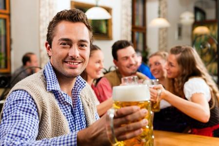 an inn: Inn or pub in Bavaria - man in traditional Tracht drinking beer