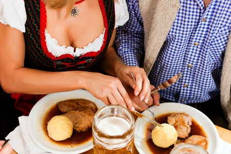 Inn or pub in Bavaria - couple in traditional Tracht drinking beer and eating roast pork with dumplings Stock Photo - 10269964