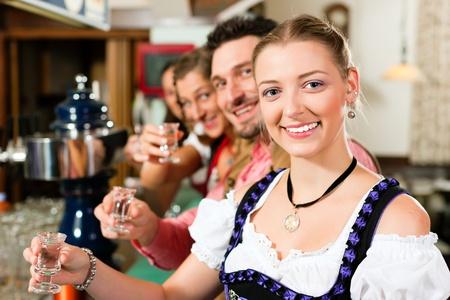 Die Menschen in bayerischen Trachten trinken Schnaps in einer Kneipe und haben Spaß