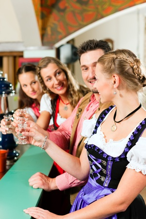 hard liquor: People in Bavarian Tracht drinking hard liquor in a pub and have fun Stock Photo