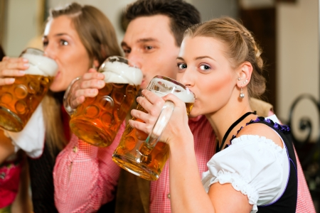 Inn or pub in Bavaria - group of three young people in traditional Tracht drinking beer  photo