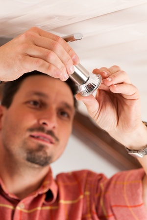 Worker is installing a luster in a Haus on the ceiling Stock Photo - 10268850