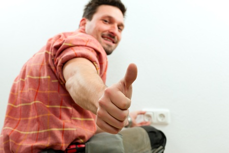 blue collar: Electrician installing a power socket giving the thumbs-up sign - focus on thumb Stock Photo