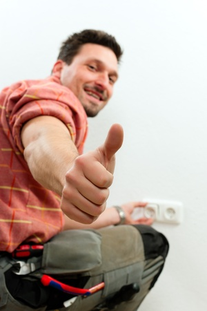 Electrician installing a power socket giving the thumbs-up sign - focus on thumb Stock Photo - 10448756