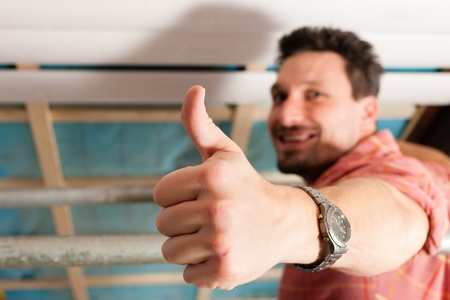 Man doing dry walling, working under a roof slope Stock Photo - 10269904