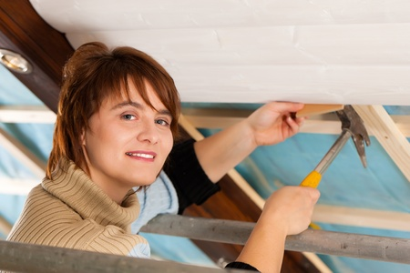 walling: Woman doing dry walling, working under a roof slope Stock Photo
