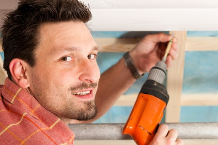 Man doing dry walling, working under a roof slope Stock Photo - 10269953