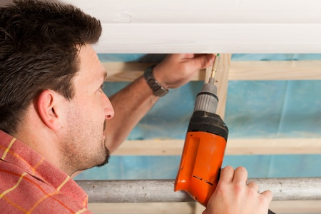 Man doing dry walling, working under a roof slope Stock Photo - 10268738