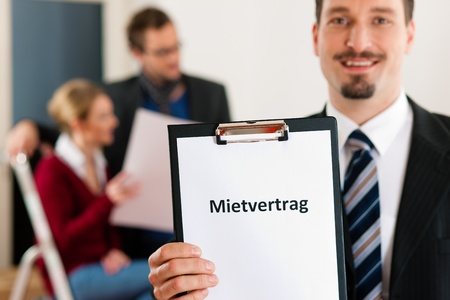 accommodation broker: Young couple renting a home or apartment, they are meeting the owner or real estate broker standing in front (the sign is written in German)