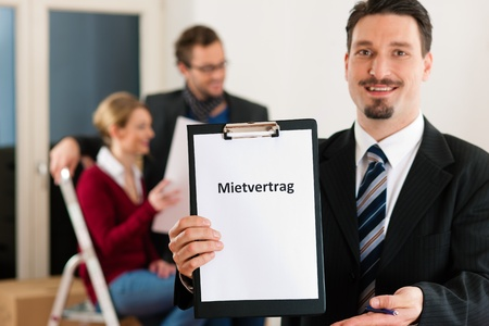 tenant: Young couple renting a home or apartment, they are meeting the owner or real estate broker standing in front (the sign is written in German)