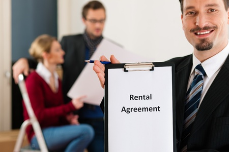 accommodation broker: Young couple renting a home or apartment, they are meeting the owner or real estate broker standing in front   Stock Photo