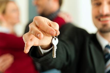 courtier: Jeune couple d'acheter ou de louer une maison ou un appartement, ils sont r�unis le propri�taire ou le courtier immobilier qui a les clefs, l'accent sur les touches