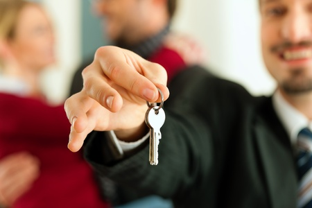 house keys: Young couple buying or renting a home or apartment, they are meeting the owner or real estate broker who has the keys; FOCUS on keys