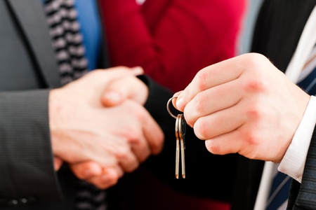 tenant: Young couple buying or renting a home or apartment, they are meeting the owner or real estate broker who has the keys; FOCUS on keys