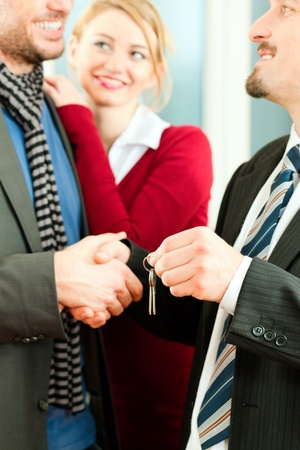 accommodation broker: Young couple buying or renting a home or apartment, they are meeting the owner or real estate broker who has the keys; FOCUS on keys
