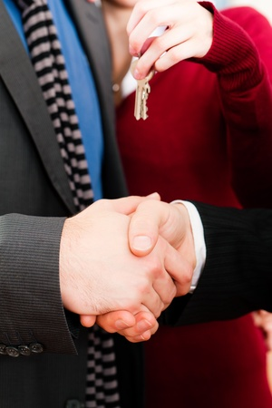 Young couple buying or renting a home or apartment, they are meeting the owner or real estate broker who has given them the keys   photo
