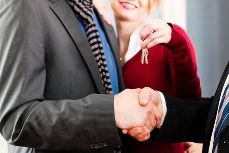 accommodation broker: Young couple buying or renting a home or apartment, they are meeting the owner or real estate broker who has given them the keys   Stock Photo