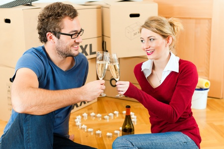 Young couple moving in a home or apartment, they are sitting on the wood floor drinking champagne having a break from renovation   photo