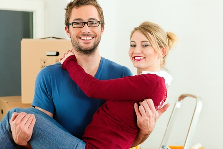 Young couple moving in a home or apartment, the man in carrying his woman photo