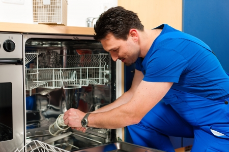 repair: Technician or plumber repairing the dishwasher in a household