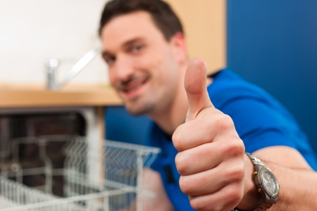 thumps up: Technician or plumber repairing the dishwasher in a household