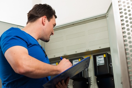 billing: Technician reading the electricity meter to check consumption Stock Photo