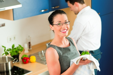 Young couple - man and woman - cooking in their kitchen at home cleaning vegetables  photo