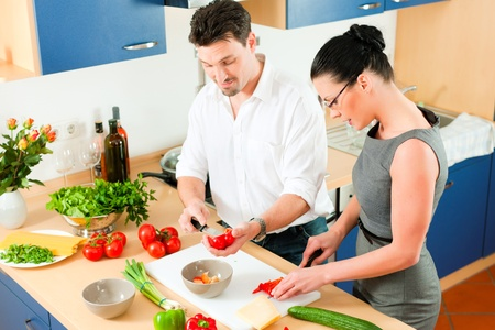 Young couple - man and woman - cooking in their kitchen at home preparing vegetables for salad and pasta sauce Stock Photo - 10269932