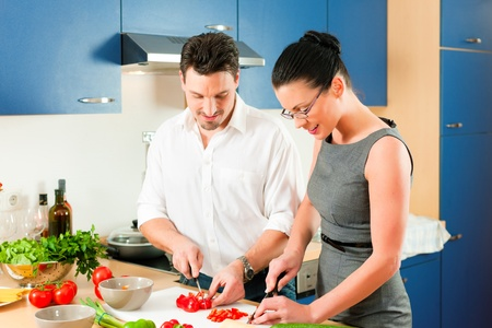 Young couple - man and woman - cooking in their kitchen at home preparing vegetables for salad and pasta sauce Stock Photo - 10269937