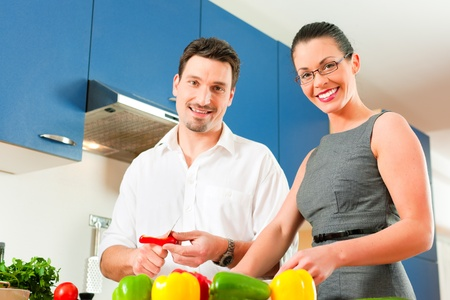 Young couple - man and woman - cooking in their kitchen at home preparing vegetables for salad and pasta sauce Stock Photo - 10269935