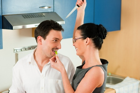 woman knife: Fun in the kitchen – woman is holding a knife over the head of her husband Stock Photo