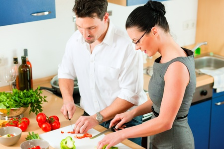 Young couple - man and woman - cooking in their kitchen at home preparing vegetables for salad and pasta sauce Stock Photo - 10268856