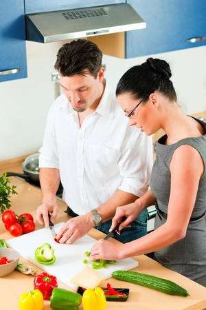 Young couple - man and woman - cooking in their kitchen at home preparing vegetables for salad and pasta sauce Stock Photo - 10269949