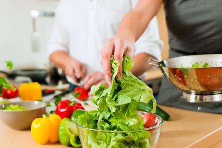 mujeres cocinando: Hombre y mujer en la cocina: se prepara la ensalada y verduras para la cena o almuerzo