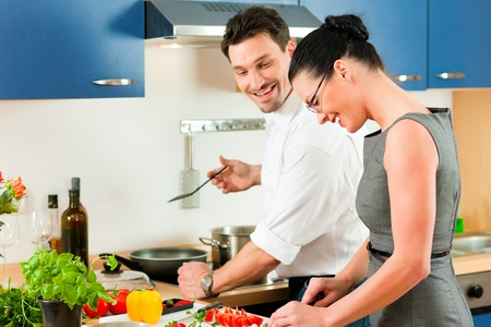romantic dinner: Young couple - man and woman - cooking in their kitchen at home preparing vegetables for salad and pasta sauce