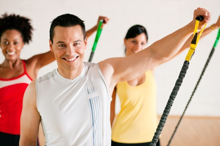 Group of three people in colorful cloths in a gym doing gymnastics with tube equipment Stock Photo - 10305993