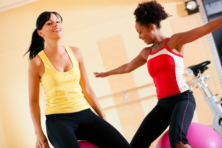 Two young, healthy women doing gymnastics exercises with a fitness ball in gym photo