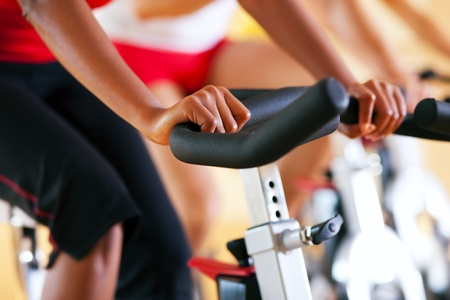 Three people spinning in the gym, exercising for their legs and cardio training Stock Photo