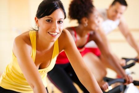krachtige vrouw: Groep van drie mensen - vermoedelijk vrienden - spinning in de sportschool,, de uitoefening van hun benen en cardio training Stockfoto