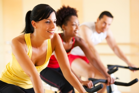 men exercising: Group of three people - presumably friends - spinning in the gym, , exercising for their legs and cardio training