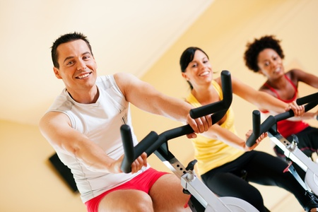 stationary bike: Group of three people - presumably friends - spinning in the gym, , exercising for their legs and cardio training