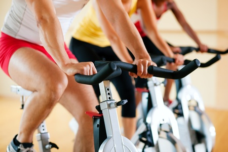 stationary bike: Three people spinning in the gym, exercising for their legs and cardio training Stock Photo
