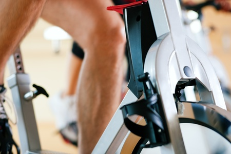 Three people spinning in the gym, exercising for their legs and cardio training photo