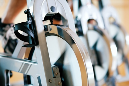 cardio fitness: Three people spinning in the gym, exercising for their legs and cardio training Stock Photo