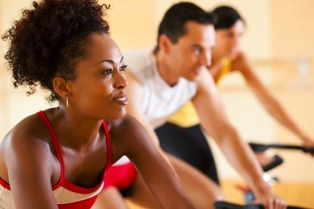 hombres haciendo ejercicio: Grupo de tres personas - presumiblemente amigos - spinning en el Gimnasio, ejercer sus piernas y entrenamiento de cardio