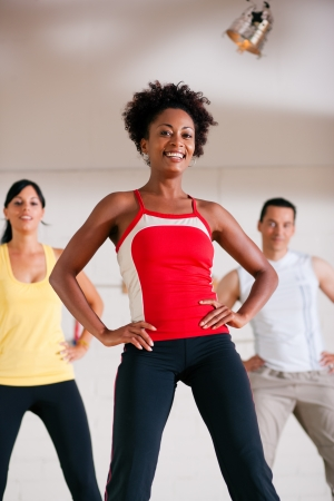 Group of three people in colorful cloths in a gym doing step gymnastics, a female instructor in front photo